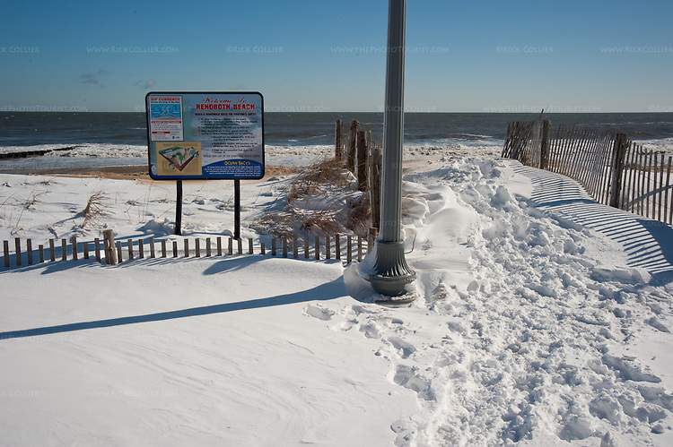 The familiar beach signs look slightly surreal against snow drifting  on the beach, dunes, and boardwalks along the beach at Rehoboth Beach, Delaware, the morning after the blizzard of February 2010.
