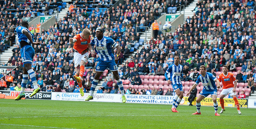 Blackpool's Andrew Keogh gets to the ball ahead of Wigan Athletic's Emmerson Boyce to open the scoring<br /> <br /> Photo by Stephen White/CameraSport<br /> <br /> Football - The Football League Sky Bet Championship - Wigan Athletic v Blackpool - Saturday 26th April 2014 - DW stadium - Wigan<br /> <br /> &copy; CameraSport - 43 Linden Ave. Countesthorpe. Leicester. England. LE8 5PG - Tel: +44 (0) 116 277 4147 - admin@camerasport.com - www.camerasport.com