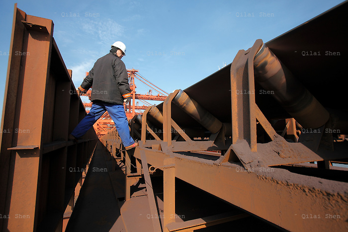 A dock worker inspects a conveyer belt at an iron-ore transfer and storage center operated by the Shanghai International Port Group in Shanghai, China on 26 January 2010. China's economic boom and hunger for natural resources has been a blessing for countries such as Australia and Brazil, who controls most the world's high quality iron ore deposits.