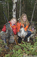 Young girls hunter holding shot ruffed grouse with their dog