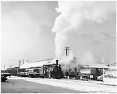 D&amp;RGW K-28 with freight train in snow next to Durango freight house.  Several 1949-1950 automobiles parked nearby.<br /> D&amp;RGW  Durango, CO  ca. 1950