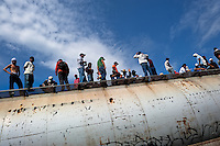 """Dozens of Central American immigrants ride atop a cargo train passing through the border area in the south of Mexico, on 25 May 2010. Between 2010 and 2015, the US and Mexico have apprehended almost 1 million illegal immigrants from El Salvador, Honduras, and Guatemala. While the economic reasons remain the most frequent motivation for people from Central America to illegally immigrate to the US, thousands of Salvadorans, Guatemalans, and Hondurans, many of them minors, seek asylum in the US due to the thriving crime and gang-related violence in their region (known as the Northern Triangle). Taking an exhausting and risky journey, riding thousands of miles atop the cargo trains, facing a physical danger and extortion from the organized crime groups that control migrant routes, the """"undocumented"""" still flee to the US, looking for their American dream."""