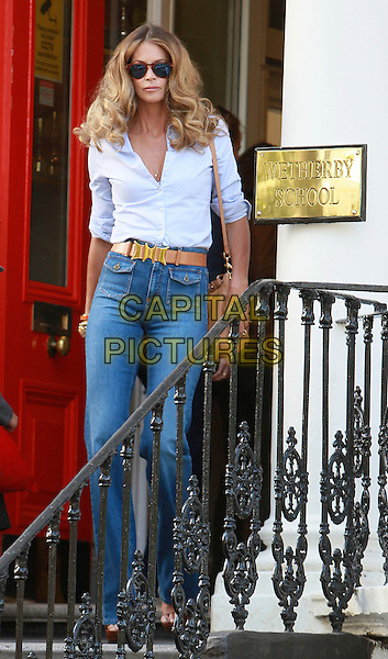 ELLE MACPHERSON.Pictured on the School Run in central London, England, UK,.April 27th 2011..full length wide leg denim jeans 70s seventies curly hair shirt white blue belt tan brown high waisted platform shoes high heels sandals sign Wetherby pockets ray bans sunglasses bag satchel mulberry .CAP/HIL.©John Hillcoat/Capital Pictures
