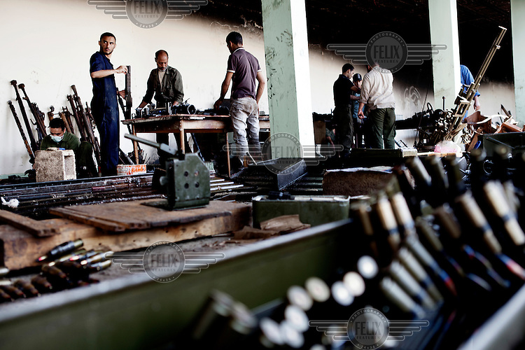 In a military base, former Gaddafi military staff and young men work on repairing guns and rockets that the old regime tried to burn before escaping the revolution. A lot of the goods still works and after some creative work they can be mounted on a pickup truck and sent to the front line for the rebels fighters to use. Bullets are being cleaned in the foreground. On 17 February 2011 Libya saw the beginnings of a revolution against the 41 year regime of Col Muammar Gaddafi..