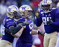 Ryan Bowman is congratulated by teammates after yet another big stop by the Husky defense.