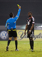 Brandon McDonald (2) of  D.C. United is given a yellow card by referee Jair Marrufo during the game at RFK Stadium in Washington, D.C. D.C. United tied the Portland Timbers, 1-1.