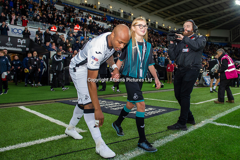 Andre Ayew of Swansea City walks out with a mascot during the Sky Bet Championship match between Swansea City and Millwall at the Liberty Stadium in Swansea, Wales, UK. Saturday 23rd November 2019