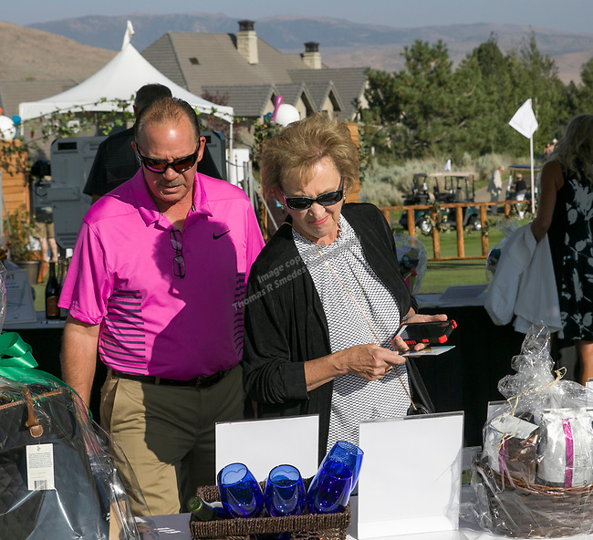 Greg and Karen Weil look at auction items during the Art of Childhood Gala and Fundraiser at Montreux Golf and Country Club on Friday, August 24, 2018.
