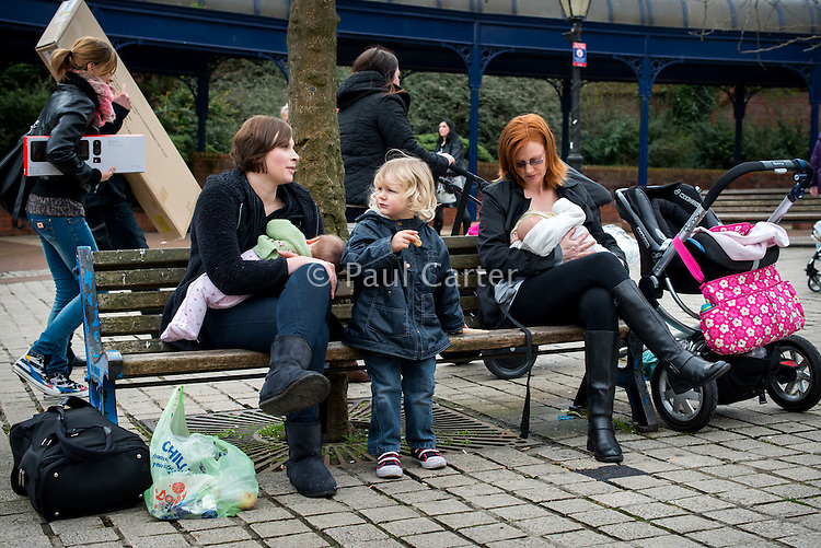 Women chat while sitting on benches in the precinct outside a supermarket and breastfeeding their babies. Other shoppers are passing by in the background.<br /> <br /> Image from the &quot;We Do It In Public&quot; documentary photography project collection: <br />  www.breastfeedinginpublic.co.uk<br /> <br /> Dorset, England, UK<br /> 17/04/2013