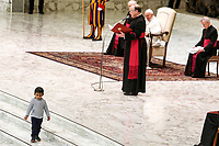 A child walks on the floor as Pope Francis attends his weekly general audience in the Paul VI hall at the Vatican, January 22, 2020.<br />