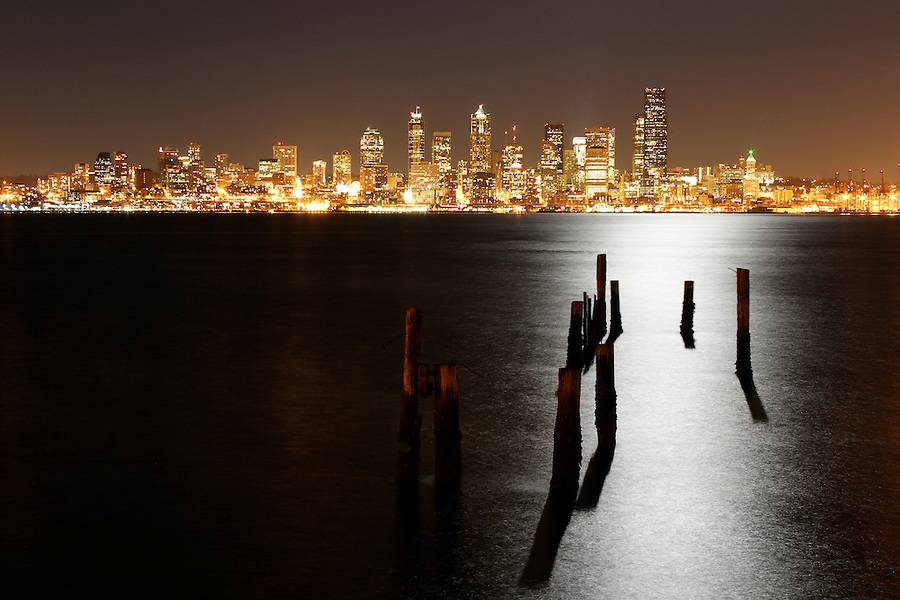 Seattle city skyline at night with pilings and light of full moon reflected in Elliot Bay, Seattle, Washington, USA