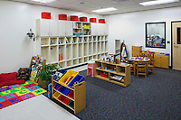 Contemporary Elementary school classroom with built-in cabinets, child scaled furniture, carpeting and observation window.