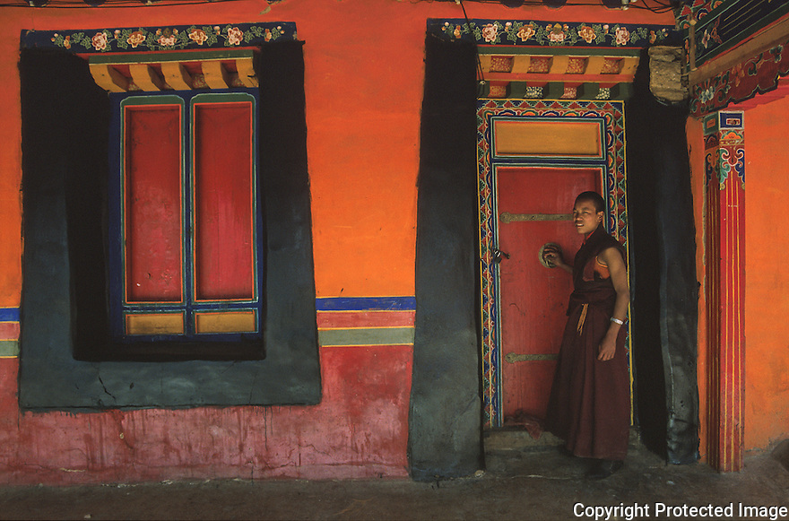 En munk i ei d¯r i Lhasa, Tibet, Kina, farger,