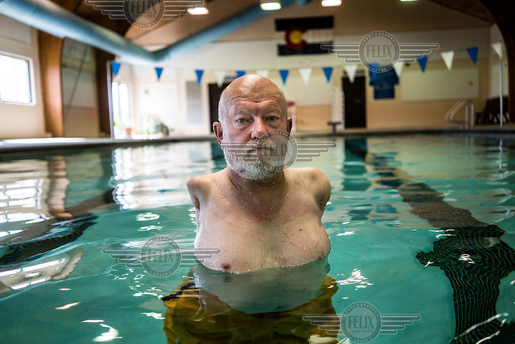 Les Baugh, 59, at the public pool in Walden, Colorado. While swimming, Les is able to mentally think through commands such as 'extend elbow' or 'rotate wrist'. He will use these when wearing the experimental mind-controlled prosthetic arms which he is testing with John Hopkins Applied Physics Lab. Baugh lost both his arms at the shoulder in a freak electrical accident 40 years ago. Since then, he has managed life mostly without the help of prosthetic arms, which he finds to be more of an uncomfortable nuisance than a help. In 2013, Les underwent a state of the art surgery called Targeted Muscle Reinnervation, where the bundle of nerves at the stump of his shoulders were remapped to his pectoralis muscles. After he recovered from surgery, researchers at Johns Hopkins Applied Physics Lab fitted him with two robotic arms, called the MPL or Modular Prosthetic Limb, and he was able to manipulate objects with his hands, just by thinking about it. The MPL is a state of the art prototype, and not ready for take-home, so Baugh has been practicing mind control at home in rural Walden using a virtual reality game paired with less advanced prosthetic limbs. At a later stage the researchers at Johns Hopkins hope to get Les to try more advanced versions of the MPL  in the hope that his remapped nerves will have grown deeper into his pecs and he'll be able to manipulate the arms more effectively.