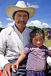 Guatemalan man poses with his daughter, outside church, San Nicolas, Western Highlands, Guatemala