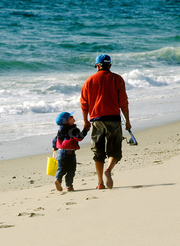 Grandfather and granddaughter walking along the beach to go fishing.<br />