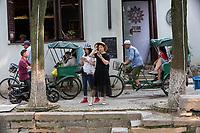 Suzhou, Jiangsu, China.  Pedicabs (Rickshaws) Transport Visitors through Tongli Ancient Town near Suzhou--a popular weekend tourist destination.