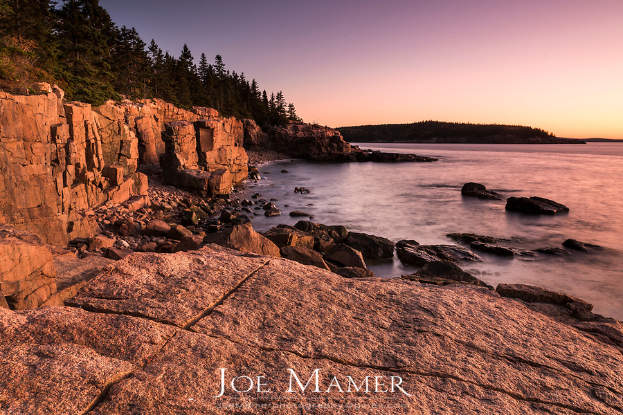 Sunrise on scarred granite coastline along Ocean Drive in Acadia National Park.