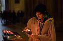 Lisboa, UK. 04.05.2015. People light candles within the Se de Lisboa (Lisbon Cathedral). Photograph © Jane Hobson.