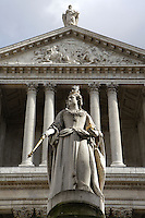 Queen Anne, a copy of the original sculpture by Francis Bird, St Paul's cathedral (1675 - 1710, architect Sir Christopher Wren) completed during her reign, wears crown and has Order of St George around her neck, sceptre pointing downwards in right hand and orb in left; portico and pediment in the background with St Paul's statue holding his sword on the top, London, England, UK Picture by Manuel Cohen