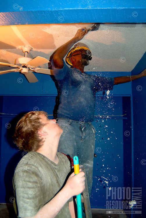 Home construction work with teenager wearing a ventalation mask while helping to scrape the ceiling with older african american man