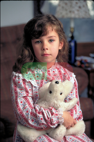 portrait of sick young girl holding teddy bear