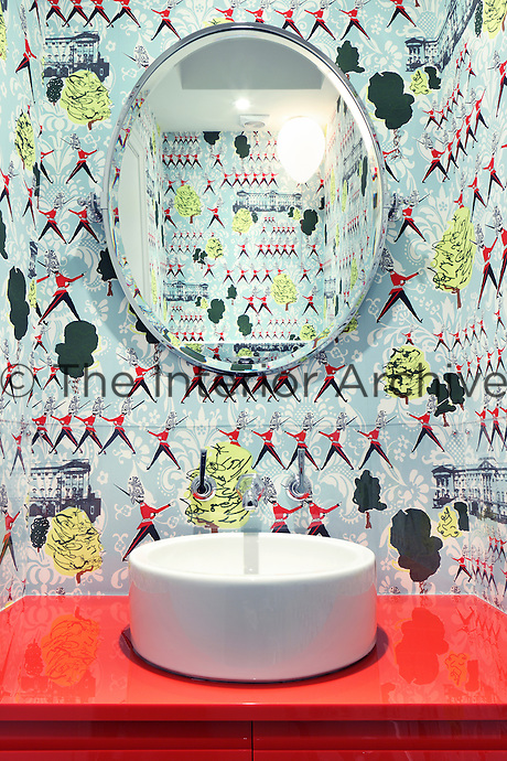 A cheerful child's bathroom with a shiny red washstand, curved wash basin and 1950s inspired wallpaper