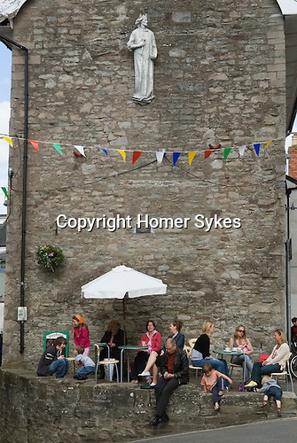 A cafe in the town square, festival goers sit under the statue of King Henry V111. The Hay Festival, Hay on Wye, Powys, Wales, Great Britain. 2006.