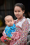 A woman holds her baby in the Tahan Market in Kalay, a town in Myanmar. This market is located in Tahan, the largely ethnic Chin section of the town. The woman is wearing thanaka, a cosmetic paste, on her face.