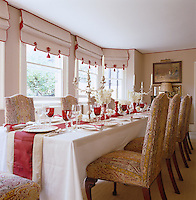 The colour scheme for the dining room is red and white with the walls and Roman blinds in a striped fabric with corresponding table linen and red glassware