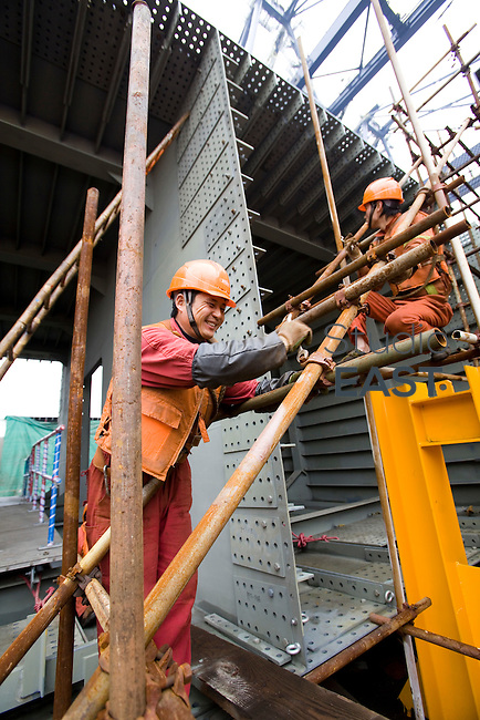 Workers dismantle scaffoldings surrounding OBGs reading for loading, on Changxing Island, Shanghai, on December 13, 2009. Photo by Lucas Schifres/Pictobank