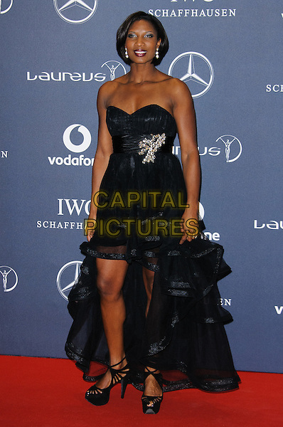 Denise Lewis.Arrivals at the Laureus 2012 World Sports Awards held at the Queen Elizabeth II Centre, London, England..February 6th, 2012.full length black strapless dress sheer tulle silver brooch waistband .CAP/CJ.©Chris Joseph/Capital Pictures.