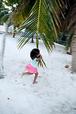 BELIZE, Caye Caulker, a young girl uses a palm leaf as a swing