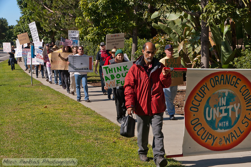 """Mohammed holds the """"Occupy Orange County"""" sign as Occupy Orange County, Irvine marchers walk down the sidewalk of Alton in Irvine, CA as a part of their Saturday protest against banks.  Many signs are visible."""