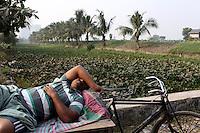 A man sleeps on a bike near farmland on the outskirts of Kolkata, India. November, 2013