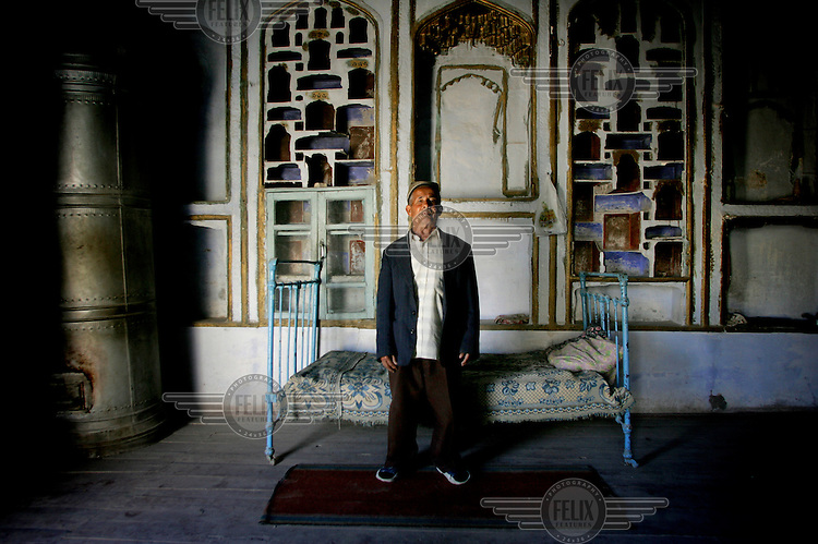 A man stands in front of an ancient iron bed at his home in the old city.