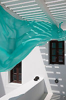 A length of turquoise silk catches the light breeze on the shaded terrace