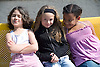 Group of girls sitting together on bench in school playground smiling,