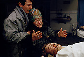 Bucharest, Romania<br /> December 24, 1989<br /> <br /> A mother in the city morgue grieves for her son who was killed in the uprising overthrowing former leader Nicolae Ceausescu.<br /> <br /> The week-long series of violence that overthrew the Communist regime of Nicolae Ceausescu, ended in a trial and execution of Ceausescu and his wife Elena by firing squad. Romania was the only Eastern Bloc country to violently overthrow its Communist regime or to execute its leaders.<br /> <br /> The Romanian populace was dissatisfied with the Communist regime and leader Ceausescu's economic and development policies were blamed for the country's shortages and widespread poverty. The powerful secret police (Securitate) controlled what was essentially a police state. Ceausescu was not pro-Soviet but &quot;independent&quot; on foreign policy. He imitated the hard-line, megalomania, and personality cults of communist leaders like North Korea's Kim Il Sung.