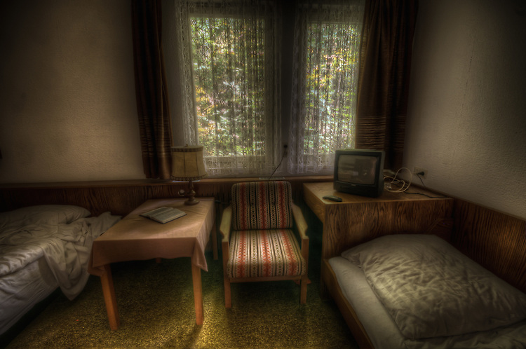 A abandoned hotel bedroom with chair and table and tv in the south of Germany