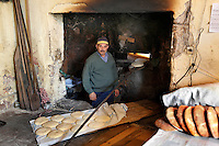 "Baker looking at the camera inside his traditional bakery with fresh baked bread in the foreground and the oven in the background, old city, Portuguese Fortified city of Mazagan, El Jadida, Morocco. El Jadida, previously known as Mazagan (Portuguese: Mazag""o), was seized in 1502 by the Portuguese, and they controlled this city until 1769. Picture by Manuel Cohen"