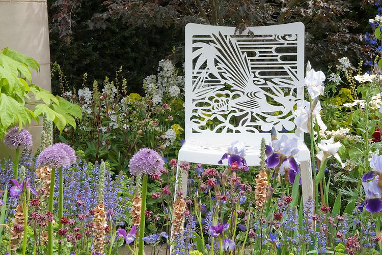 Garden Chair with Bird Ornamentation Detal in Flower garden in spring