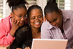 Grandmother and granddaughters looking at laptop