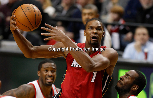 Miami Heat center Chris Bosh (1) drives to the basket against Portland Trail Blazers shooting guard Wesley Matthews (L) and center J.J. Hickson (R) during first quarter of their NBA basketball game in Portland, Oregon, January 10, 2013.  REUTERS/Steve Dipaola (UNITED STATES)