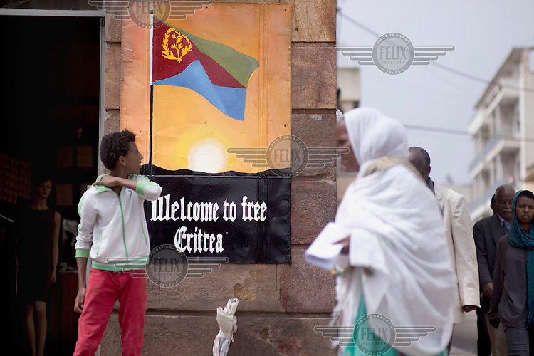 Pedestrians walking along the main road passes a poster with the slogan 'Welcome to Free Eritrea', celebrating the 1991 independence.