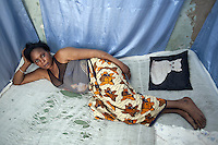 Senegal. Dakar. Marie is a sex worker. She lies on the bed used with her customers. Pillow with a cat. Marie has been approched by ENDA Sante within the programme framework of the Global Fund and ANCS (Alliance Nationale contre le Sida). ENDA Sante is in charge of the component Advocacy prevention and care of vulnerable groups, such as sex workers, in a fight towards HIV Aids. The Global fund supports ANCS and ENDA Sante with a financial grant. 08.12.09 © 2009 Didier Ruef