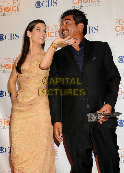 SANDRA BULLOCK & GEORGE LOPEZ .36th Annual People's Choice Awards - Press Room held at the Nokia Theatre LA Live, Los Angeles, California, USA, 6th January 2010..half length dress award trophy winner beige gold earrings one shoulder strap bare off the hand black suit funny touching chin face blue shirt bracelet cuff .CAP/ADM/BP.©Byron Purvis/Admedia/Capital Pictures