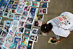 A woman helps lay out photos on the ground in Puerto Madero, Mexico, on December 17, 2013. The photos were brought by a caravan of Central Americans, mostly mothers looking for their disappeared or trafficked children, who came to Mexico for 17 days.