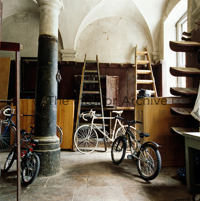 Bikes and ladders are stored in the disused stable block