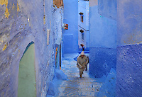 Man wearing a djellaba climbing the steps of a narrow street painted blue in the medina or old town of Chefchaouen in the Rif mountains of North West Morocco. Chefchaouen was founded in 1471 by Moulay Ali Ben Moussa Ben Rashid El Alami to house the muslims expelled from Andalusia. It is famous for its blue painted houses, originated by the Jewish community, and is listed by UNESCO under the Intangible Cultural Heritage of Humanity. Picture by Manuel Cohen